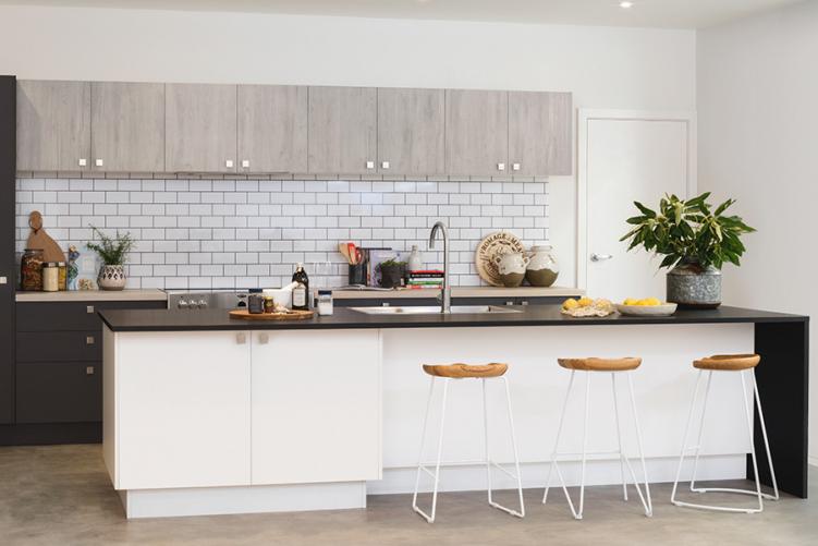 Large white kitchen island with dark benchtop