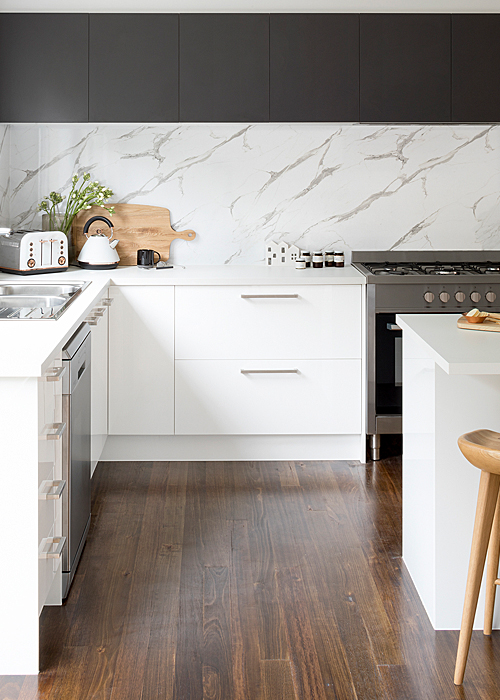 white kitchen with black wall cabinets and marble splashback